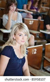 Portrait of college girl sitting in auditorium with classmates in background
