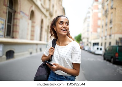 Portrait of college student sitting outside with mobile phone and looking away