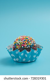 Portrait of colorful chocolate cake ball in blue background with empty space for text