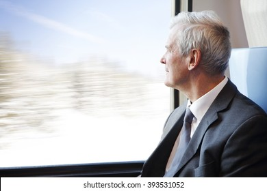 Portrait of commuter senior businessman traveling by train and looking through window the winter landscape