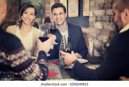 Portrait of company men and women in restaurant with a glass wine