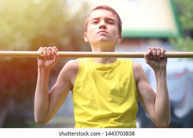 Portrait of concentrated boy in yellow T-shirt doing pull ups on horizontal bar outdoors. Healthy lifestyle concept. Blurred background