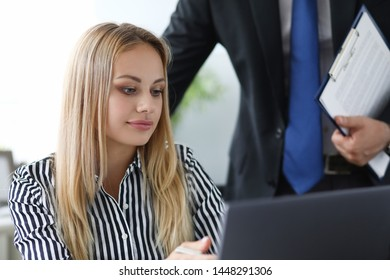 Portrait of concentrated businesswoman with partner. Beautiful woman working on laptop at modern workplace. Biz and company concept. Blurred background