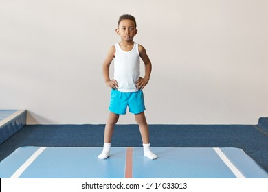 Portrait of concentrated dark skinned boy dressed in white shirt, socks and blue shorts doing physical exercises to warm up body before boxing training, standing on mat with hands on his waist
