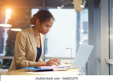 Portrait of concentrated female administrative manager monitoring fate of official site while monitoring work of freelancers sitting in coworking space using laptop computer and wireless connection