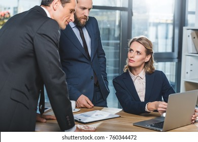 portrait of concentrated lawyers using laptop together during work in office