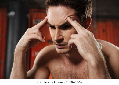 Portrait of concentrated man with headache sitting in a gym. Looking aside.