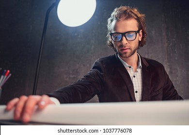 Portrait of concentrated man leaning on desk by hand and looking at blueprint. Centralization during work concept. Low angle