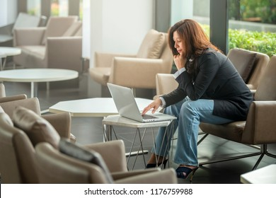 Portrait of a concentrated mature business woman working on a laptop while sitting at the table at office.