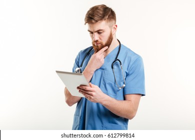 Portrait of a concentrated pensive medical doctor or nurse thinking while looking at tablet computer isolated on white background