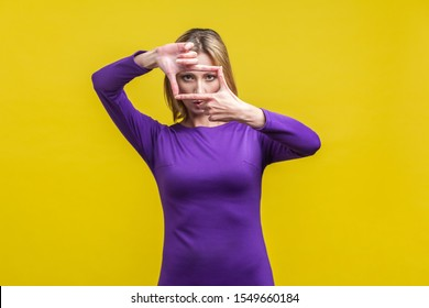 Portrait of concentrated woman in elegant tight purple dress looking at camera through hand frame, capturing photo or focusing eyesight on target. indoor studio shot isolated on yellow background