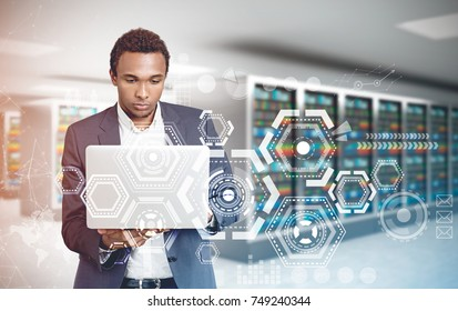 Portrait of a concentrated young African American businessman wearing a suit and looking attentively at his white laptop screen. Server room background, HUD. Toned image double exposure mock up