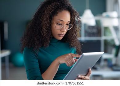 オフィスに立ちながら、デジタルタブレットを使用した、集中した若い起業家女性のポートレート。