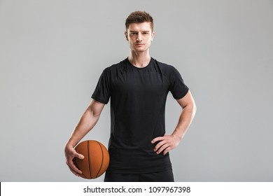 Portrait of a concentrated young sportsman holding basketball isolated over gray background