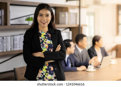 Portrait of confidence Businesswoman stand in front of table in meeting room in cafe with business team in background using for coporate background work
