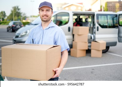 Portrait of confidence express courier next to his delivery van