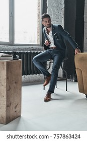 Portrait of confidence. Full length of thoughtful young man in full suit looking away while sitting on the stool