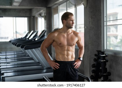 Portrait of confidence muscular man standing in the sport gym. Man exercise. gym, sport, rope, workout and exercises concept