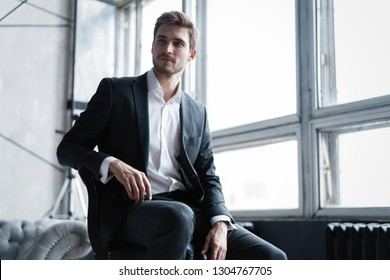 Portrait of confidence. Thoughtful young man in full suit looking away while sitting on the stool.