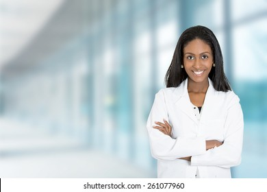 Portrait confident African American female doctor medical professional standing isolated on hospital clinic  hallway windows background. Positive face expression