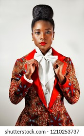 Portrait of a confident African business woman  wearing an African print suit with a sophisticated hair holding her bow tie