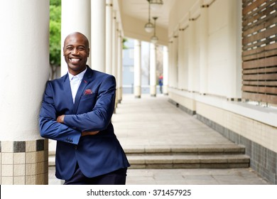 Portrait of confident african businessman standing outdoors with his arms crossed