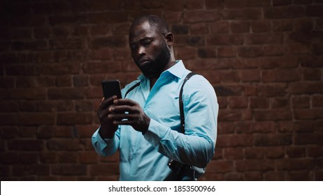 Portrait of confident african detective with holsters using smartphone isolated on red brick wall background. Handsome afro cop reading information on mobile phone - Shutterstock ID 1853500966