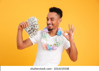 Portrait of a confident african man dressed in summer outfit holding bunch of money banknotes and showing ok gesture isolated over yellow background