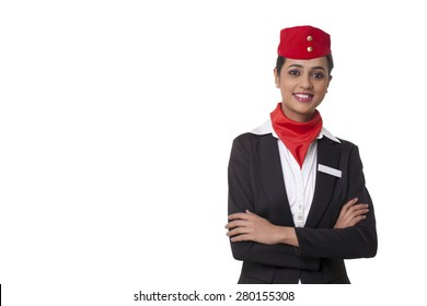 Portrait of a confident air hostess standing against white background