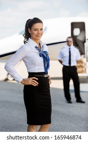 Portrait of confident airhostess with hands on hip smiling against pilot and private jet at airport terminal