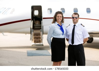 Portrait of confident airhostess and pilot standing against private jet