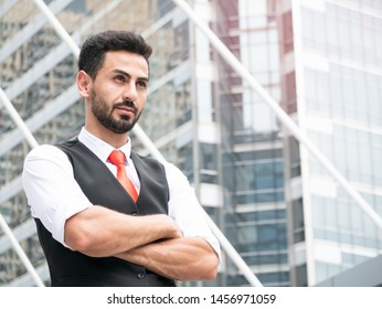Portrait of confident arab businessman manager standing with arms crossed outdoor at front modern office.