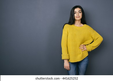 Portrait of confident Armenian girl looking at camera while posing against of grey background
