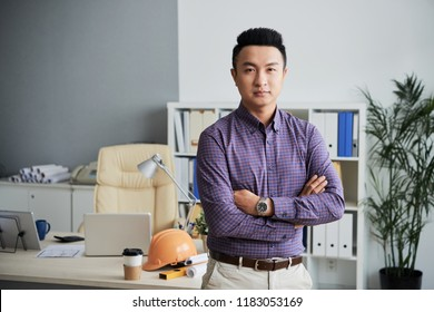 Portrait of confident Asian architect standing with his arms folded and looking at camera