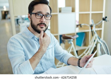 Portrait of confident Asian business man working with tablet device in creative office space and looking at camera