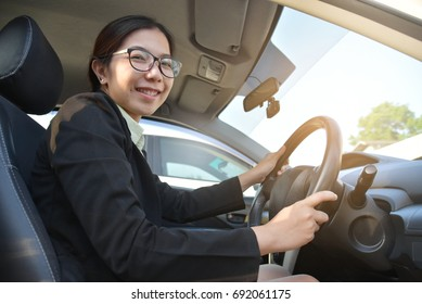 Portrait Confident Asian Business woman in black suit driving a car looking to camera. Smiling face.