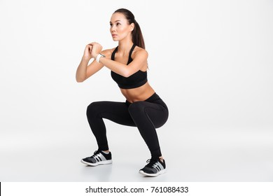Portrait of a confident asian fitness woman doing squats isolated over white background