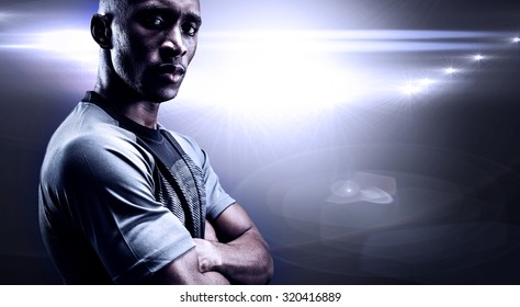 Portrait of confident athlete with arms crossed against spotlights