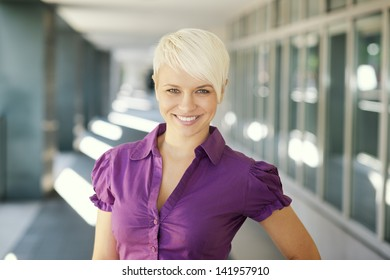 portrait of confident attractive business woman smiling and looking at camera out of office building