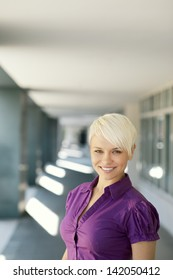 portrait of confident attractive business woman smiling and looking at camera out of office building. Copy space