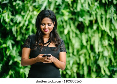 Portrait of a confident and attractive Indian Asian lawyer texting on her smartphone against a wall of plants in the background. She is wearing an elegant and professional black dress and is smiling.