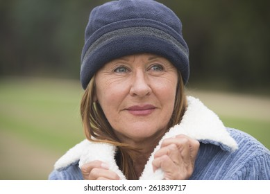 Portrait confident attractive mature woman outdoor, wearing warm bonnet and wool jacket, blurred green background.