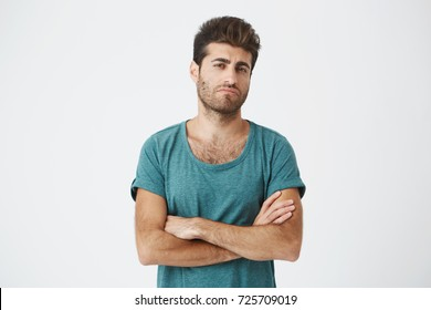 Portrait of confident attractive young spanish guy in blue tshirt and stylish haircut, crossing hands, being super jealous seeing ex girlfriend with new man.