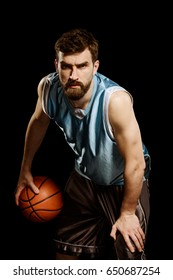 Portrait of confident basketball player on black. Young bearded man dressed in sportswear throws a serious look at the camera.