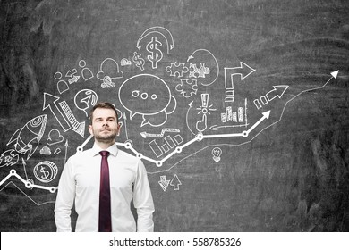 Portrait of a confident bearded businessman standing near a blackboard wall with a white growing graph and business icons above it.