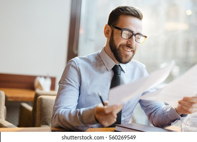 Portrait of confident bearded entrepreneur sitting at table in restaurant, holding business papers and smiling happily after reading terms profitable for his company.