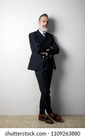 Portrait of confident bearded middle aged gentleman wearing trendy suit standing over empty white background. Studio shot. Vertical.
