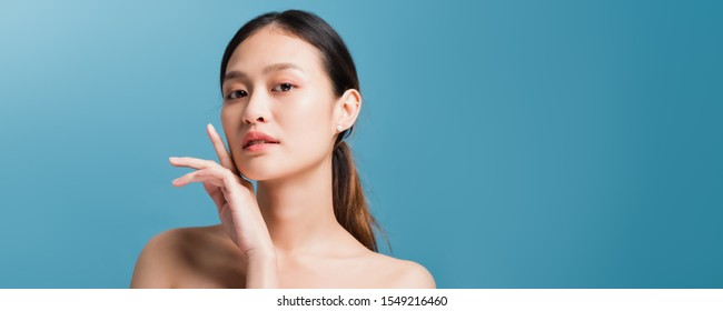 Portrait of confident beautiful asian woman with hand beside face and looking to camera isolated on blue color background with studio shot.Skincare for healthy face concept.