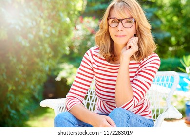 Portrait of confident and beautiful middle aged woman sitting outdoor and relaxing in the garden.