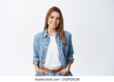 Portrait of confident beautiful woman with short hair, wearing casual clothes, standing in relaxed pose with hands in pockets, smiling with white teeth at camera, studio background